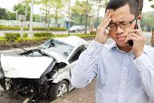 stock photo of upset  - upset driver talking on mobile phone with crash car - JPG