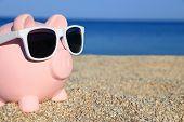 stock photo of piggy  - Summer piggy bank with sunglasses on the beach - JPG