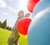 stock photo of helium  - Young boy with helium balloons walking in green meadow - JPG