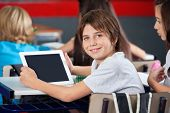 image of schoolboys  - Portrait of schoolboy holding digital tablet while sitting with classmates in classroom - JPG