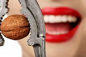 foto of strangle  - smiling woman strangles walnut with steel nutcracker - JPG