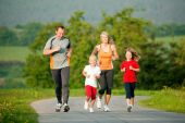 stock photo of family fun  - Family jogging outdoors with the kids in a beautiful summer landscape in the late afternoon sun - JPG
