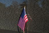 image of memorial  - This is an image of a US flag leaning on the Vietnam Memorial Wall - JPG