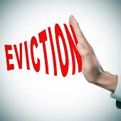 stock photo of eviction  - man hand stopping the word eviction - JPG