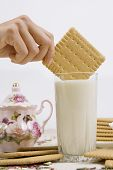 image of buttermilk  - A person dunking a cookie in a glass of buttermilk  - JPG