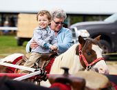 pic of carnival ride  - A happy boy rides a pony for the first time with his grandmother supporting him by his side - JPG