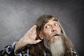 stock photo of deaf  - Senior man tries to listen sound - JPG