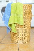 stock photo of dirty-laundry  - Dirty clothes basket with towels waiting for laundry with washing machine in backround - JPG