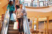 stock photo of escalator  - Male Shopper On Escalator In Shopping Mall - JPG