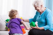 picture of grandma  - Grandma playing with her grandchild on couch - JPG