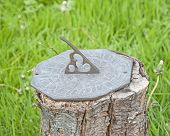 picture of sundial  - Ornate brass sundial ornament on tree stump in rural garden setting - JPG