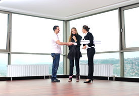 picture of real-estate agent  - happy young couple buying new home with real estate agent and looking big comfort bright apartment plans and taking key - JPG