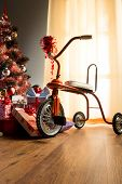 stock photo of tricycle  - Vintage christmas with decorated tree gifts and retro tricycle - JPG