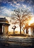 stock photo of natarajasana  - Man doing yoga near ancient ruins on Hemakuta hill in Hampi Karnataka India - JPG