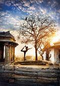 stock photo of karnataka  - Man doing yoga near ancient ruins on Hemakuta hill in Hampi Karnataka India - JPG