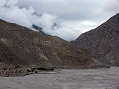 stock photo of mustang  - Monsoon clouds building up near a river in the dry Annapurna Himalayas of Mustang Nepal - JPG