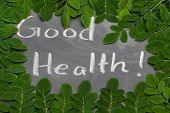 pic of moringa oleifera  - Moringa leaves with Good Health written in a slate by whtie chalk - JPG