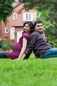stock photo of east-indian  - Image of an East Indian man sitting outside with his pregnant wife