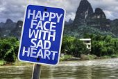 foto of loveless  - Happy Face With Sad Heart sign with a exotic background - JPG