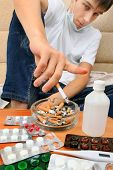 picture of teen smoking  - Sick Teenager smoking Cigarette on the Sofa with the Pills on foreground - JPG