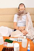 picture of home remedy  - Sick Teenager on the Sofa at the Home with Pills on foreground - JPG
