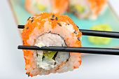 foto of masago  - Sushi roll with black chopsticks and other rolls on the background - JPG