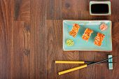 picture of masago  - Sushi rolls with masago served on turquoise plate with pickled ginger soy sauce and chopsticks on wooden table - JPG