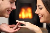 foto of propose  - Couple looking a engagement ring after proposal at home with a fire place in the background - JPG