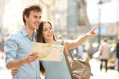 stock photo of family planning  - Couple of tourists consulting a city guide searching locations in the street and pointing - JPG