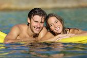 picture of bathing  - Happy couple bathing on the beach in summer vacation with a perfect white smile and looking at camera - JPG