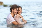 stock photo of bathing  - Happy couple in love hugging and bathing on the beach and looking away - JPG