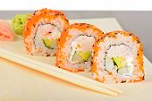 pic of masago  - Closeup California maki sushi with masago on the wooden plate - JPG