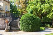 stock photo of wrought iron  - Old stone stairway of a palace with wrought iron banister in a park - JPG