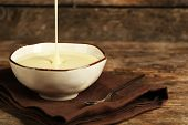 pic of condensation  - Bowl with condensed milk on napkin on wooden background - JPG