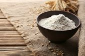 foto of sackcloth  - Flour in bowl with ears and grains on sackcloth background - JPG