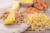 stock photo of sackcloth  - Different types of pasta on sackcloth background - JPG
