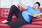 stock photo of obese man  - Overweight man eats pizza while watching tv at home - JPG