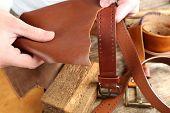stock photo of leather tool  - Repairing leather belt in workshop - JPG