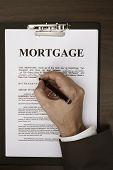 image of fill  - Man hands filling out mortgage form on desk - JPG