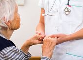 foto of geriatric  - Young doctor giving helping hands for elderly woman - JPG