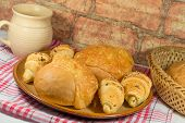 pic of bread rolls  - Bun with cheese and bread rolls with a cup in the background - JPG