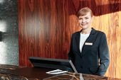 stock photo of receptionist  - Beautiful stylish hotel receptionist standing behind the service desk in a hotel lobby looking at a guest with a friendly smile - JPG