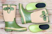 foto of clog  - Stylish footwear for a fashionable gardener with green and beige decorative gumboots and green clogs lying on rustic wooden boards viewed from above - JPG