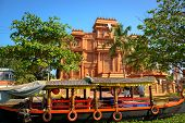 stock photo of alleppey  - Traditional Indian boat and historic building at background in Allepey - JPG