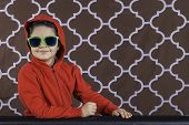 pic of hoodie  - A portrait of a young boy smiling wearing a red hoodie and green sunglasses - JPG