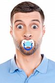picture of pacifier  - Funny young man with big eyes and pacifier in his mouth staring at camera while standing against white background - JPG