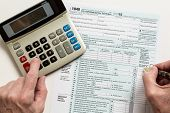 stock photo of irs  - Male caucasian hand holding pen above USA tax form 1040 for year 2015 and calculator illustrating completion of tax forms for the IRS - JPG