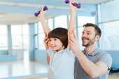 picture of physical education  - Happy father supporting his son in weight training while both standing in health club - JPG