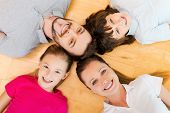 stock photo of family bonding  - Top view of happy family of four bonding to each other heads and smiling while lying on the h floor - JPG
