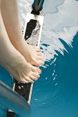 foto of wet feet  - Beautiful female feet on the steps of the pool - JPG
